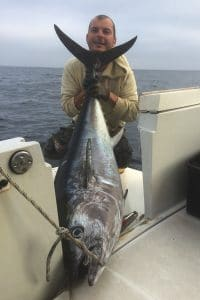 Happy capitain with a good sized tuna on his boat during the autumn season