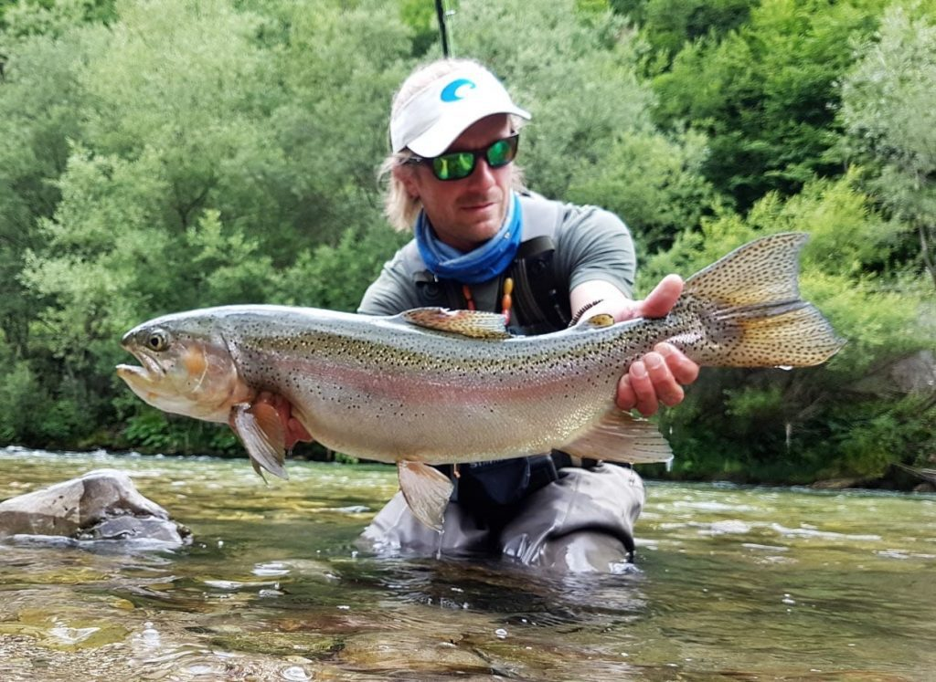 Fly fisherman with a nice Rainbow trout from Idrijca river