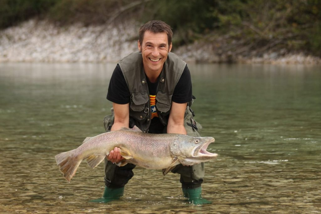 Fly fisherman with a big trout on Soča river
